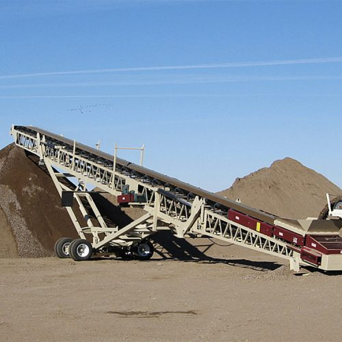 Portable radial stacking conveyor stockpiling bulk material